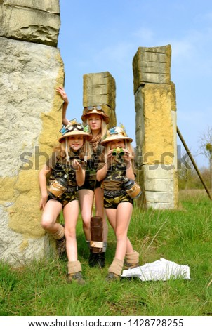 Twin young sisters and an adult girl dress up as explorers. They pose in the outdoors dressed with jungle hats and khaki safari clothes. #1428728255