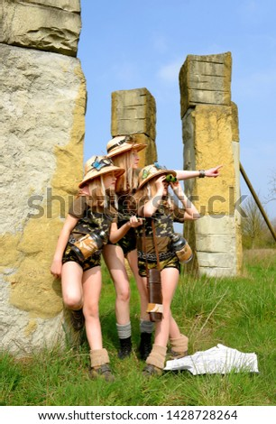 Twin young sisters and an adult girl dress up as explorers. They pose in the outdoors dressed with jungle hats and khaki safari clothes. #1428728264
