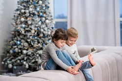 twins - boy and girl sitting on the back of the couch looking on their legs, playing brother and sister with the decorated new year pine tree on the background