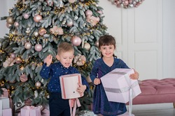 twins - boy and girl 5 years, holding the presents  before the new year pink, stylish pine tree and happily waiting for the holidays