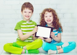 Twins boy and girls with the tablet PC on a light background. Holding thumbs up.