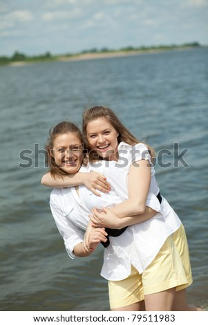 twins girls hugging and laughing with one best man on the shore