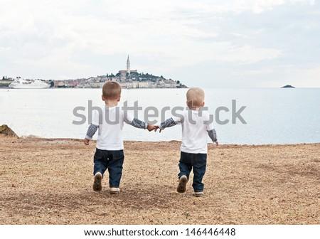 Twins go by a hand on a beach in the evening. Rovinj. Croatia.