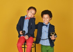 Twins. Retro. Kids smiling. Mixed kids with retro phone. Stylish kids.