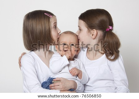 Twins sisters with baby boy brother on white background