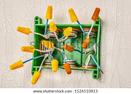 Twist-on wire connector. The use of a screw-on connection clamp for connecting and insulating electrical wires during the installation of a rectangular plastic distribution box in household wiring. #1526510813