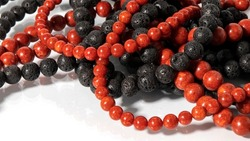 Twisted beads made of volcanic lava and red coral on a white background. Isolated jewelry. Red and black stone texture.