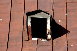 Twisted damaged broken old roof window frame without glass on top of abandoned suburban family house roof covered with rusted cracked metal roof tiles on warm sunny spring day