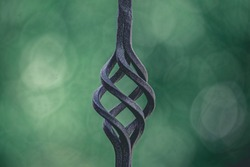Twisted decorative element of the metal fence. Against the background of a blury gray-green background with a side.