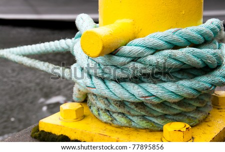 Twisted green rope round a yellow pier