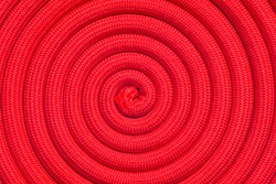 Twisted red rope. Full frame of rope arranged in a spiral shape