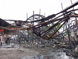 Twisted steel beams after a factory fire. Warehouse destroyed by fire. Twisted metal, pile of burnt rubble.