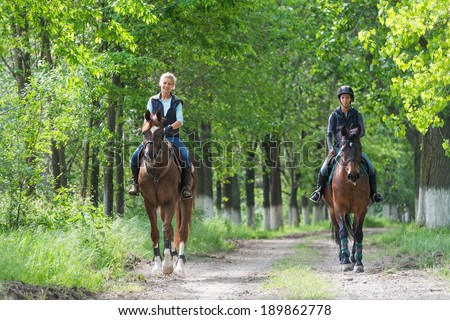 Two a young girls on horseback riding