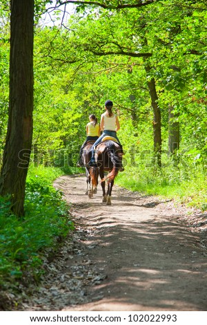 Two a young girls on horseback riding in the route