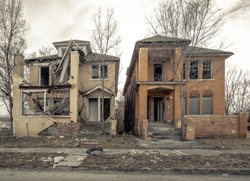 Two abandoned and decaying houses side by side in Detroit with blank sky