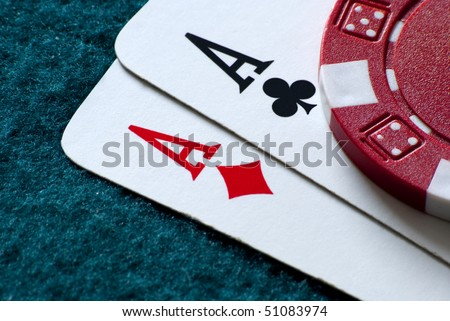 two aces and a chip on a gambling table