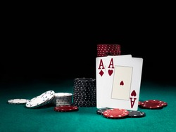 Two aces hearts and diamonds standing leaning on chips piles, some of them laying nearby on green cover of playing table. Black background. Close-up.