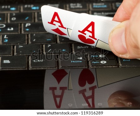 Two aces on a computer keyboard with a reflection.
