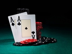 Two aces standing leaning on chips piles, some of them laying nearby on green cover of playing table. Black background. Close-up.