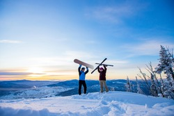 Two active friends snowboarder and skier standing on mountain top blue sky sunrise. Concept ski resort winter forest.