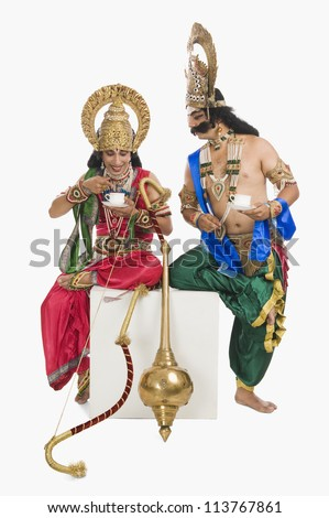 Two actors dressed-up as Rama and Ravana and drinking tea