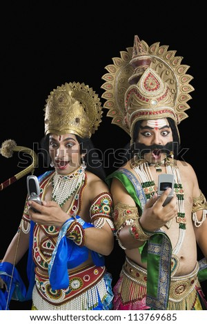 Two actors dressed-up as Rama and Ravana and reading text message