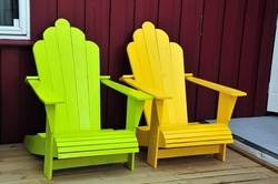Two Adirondack chairs against red house wall.  Patio with lime green and yellow deck chairs.