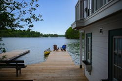 Two Adirondack chairs on a cottage wooden dock facing the blue water of a lake in Muskoka, Ontario Canada. A yellow canoe is tied to the dock. Life jacket and oars are visible near the chairs.