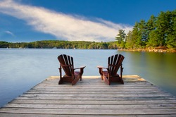 Two Adirondack chairs on a wooden dock facing a calm blue lake. Cottages nestled between green trees are visible across the water.