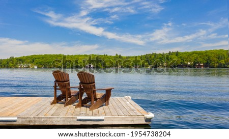 Two Adirondack chairs on a wooden dock facing a lake in Muskoka, Ontario Canada during a sunny summer morning. Cottages are nested between trees across the water. Сток-фото ©