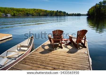 Two Adirondack chairs on a wooden dock facing the blue water of a lake in Muskoka, Ontario Canada. Life jackets are visible near the chairs. A canoe is tied to the pier, paddles are stored inside.