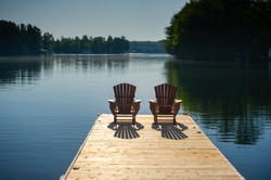Two Adirondack chairs on a wooden dock overlooking a calm lake in Ontario cottage country. Retirement planning.