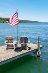 Two Adirondack Chairs on Wooden Pier with Waving American Flag and Background of Turquoise Lake Water, Tree Covered Hill and Blue Sky