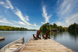Two Adirondack chairs sit on a wooden dock facing the blue waters of a calm lake. A canoe is tied to the dock. In the background there's a brown cottage nestled between trees.