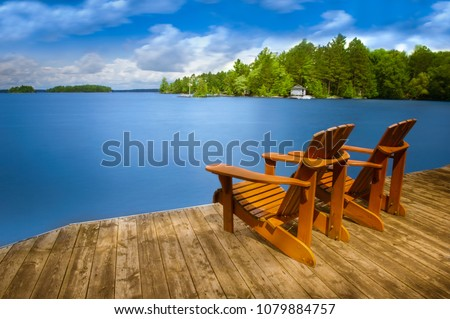 Two Adirondack chairs sitting on a wooden dock facing a blue calm lake. Across the water is a white cottage nestled among green trees.  #1079884757