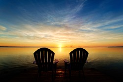 Two adirondack chairs waiting at the end of a dock to enjoy the early morning sunrise
