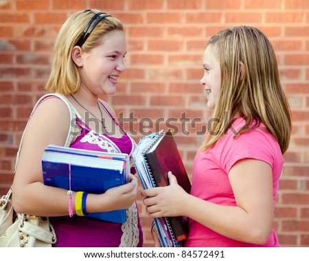 Two adolescent or teen girls talking outside school during fall