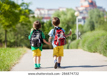 Two adorable boys in colorful clothes and backpacks, walking away, holding and eating ice cream on a sunny summer afternoon, warm day, casual clothing