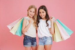 Two adorable caucasian girls 8-10 in casual clothing smiling at camera and holding colorful shopping bags with purchases isolated over pink background