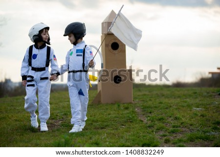 Two adorable children, boy brothers, playing in park on sunset, dressed like astronauts, imagining they are flying on the moon #1408832249