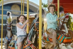 Two adorable children on the carousel having fun on holidays. Cute boy and girl look right in the camera with happy faces.