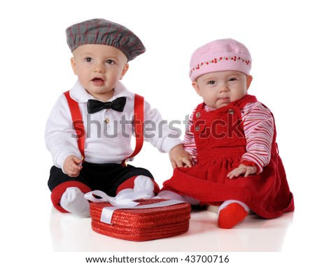 Two adorable dressed-up babies celebrating Valentine's Day.  She gives a skeptical eye as he holds her hand.  Isolated on white.