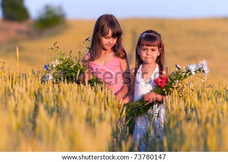 Two adorable girls with bouquets of flowers in a field of wheat