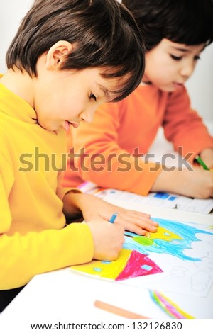 two adorable happy children drawing with crayons - stock photo