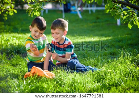 two Adorable kid boy making fire on paper with a magnifying glass outdoors, on sunny day. Child exploring fire nature in the garden. Young explorer with magnifier. Education and discovery concept