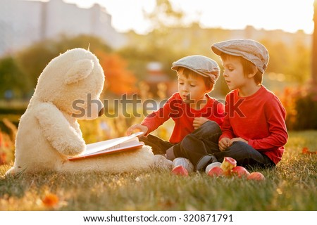 Two adorable little boys with teddy bear friend in the park on sunset, nice back light #320871791