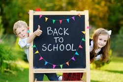 Two adorable little schoolkids feeling very excited about going back to school