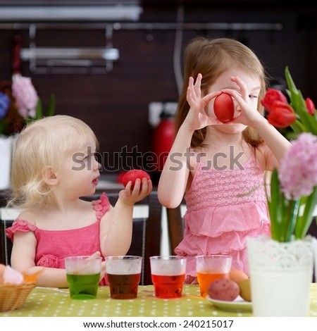 Two adorable little sisters painting Easter eggs - stock photo