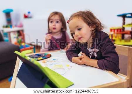 Two adorable little sisters playing with a digital tablet at home.