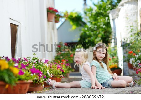 Two adorable little sisters sitting among flowers pots on warm and sunny summer day in italian town